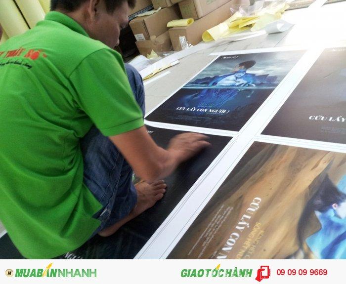 Nhân viên gia công thực hiện gia công cán bồi format cho poster, banner khach hàng đặ...