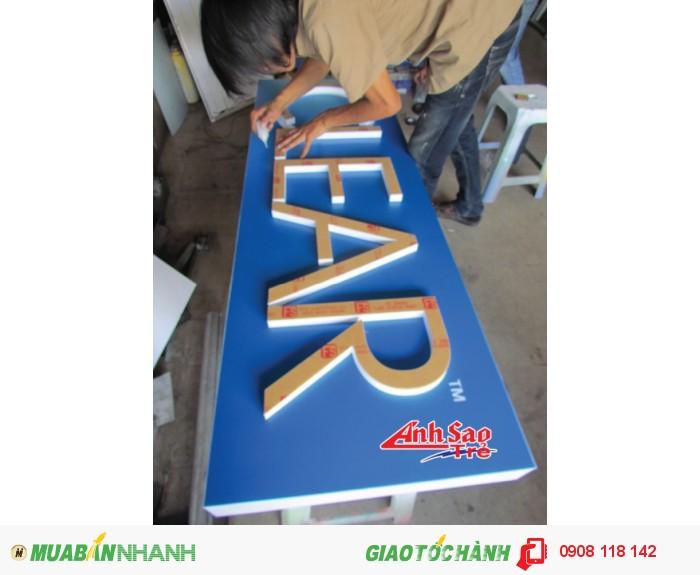 Đội ngũ nhân viên Ánh Sao Trẻ đang thiết kế bảng hiệu chữ nổi mica.