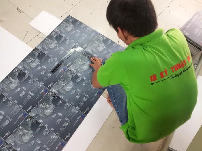 Thợ gia công in ấn thực hiện cắt thành phẩm menu PP cán format trước khi đóng th...
