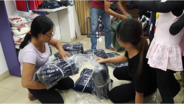 Xưởng may quần áo trẻ em may hàng thời trang trẻ em chất lượng | Nhân viên đang soạn hàng tại cửa hàng giao cho khách hàng sỉ