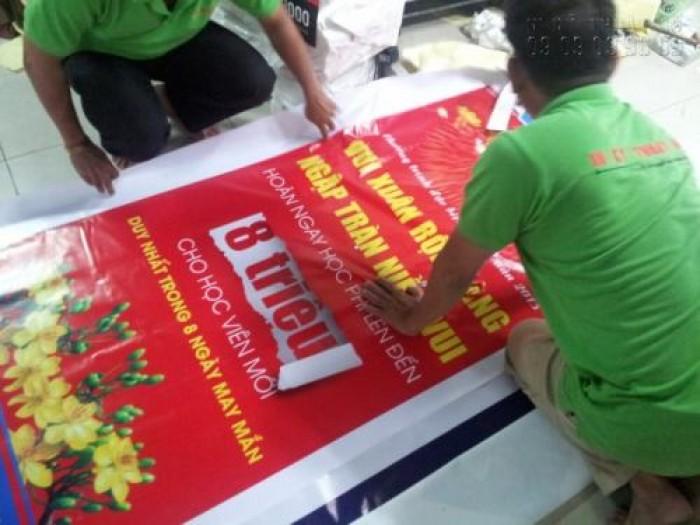 Nhân viên gia công In Kỹ Thuật Số thực hiện cuốn biên, đóng khoen poster in từ chất liệu hiflex