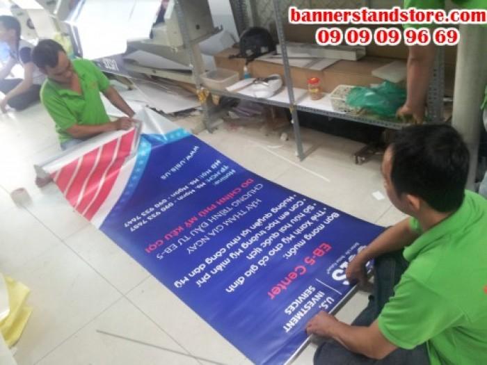 Nhân viên gia công thực hiện lắp poster vào banner cuốn cho khách hàng - khi sử dụng, chỉ cần thao tác kéo dựng lên