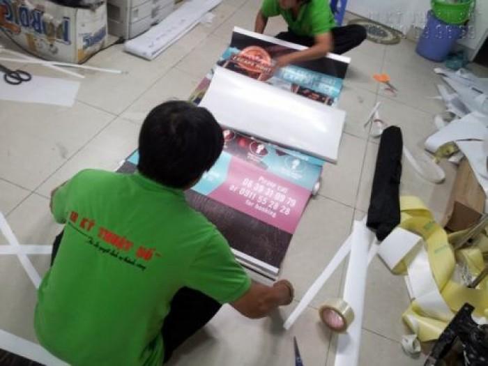 Nhân viên gia công thực hiện lắp poster vào banner cuốn cho khách hàng - khi sử dụng, chỉ cần thao tác kéo dựng lên3
