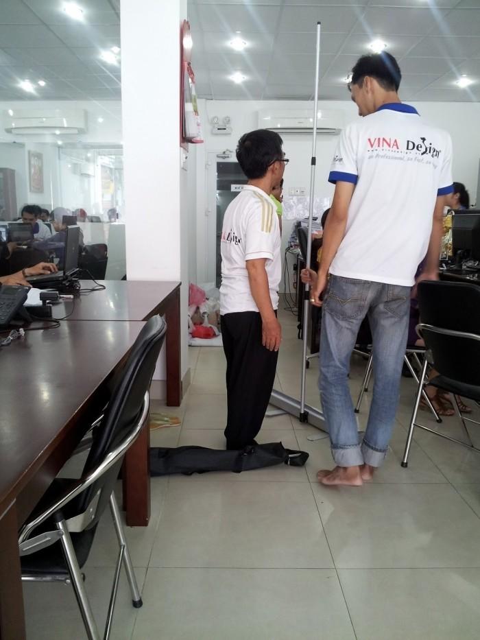 Nhân viên In Kỹ Thuật Số hướng dẫn cách sử dụng banner cuốn cho khách hàng tại văn phòng công ty4