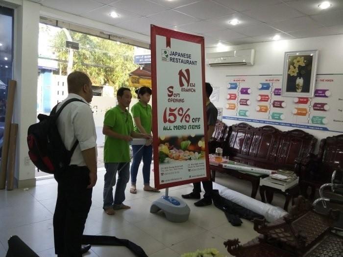 Nhân viên In Kỹ Thuật Số đang lắp mẫu poster lên standee đế nước 2 mặt cho khách hàng