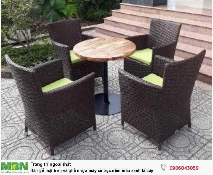 Bàn gỗ mặt tròn và ghế nhựa mây có bọc nệm màu xanh lá cây