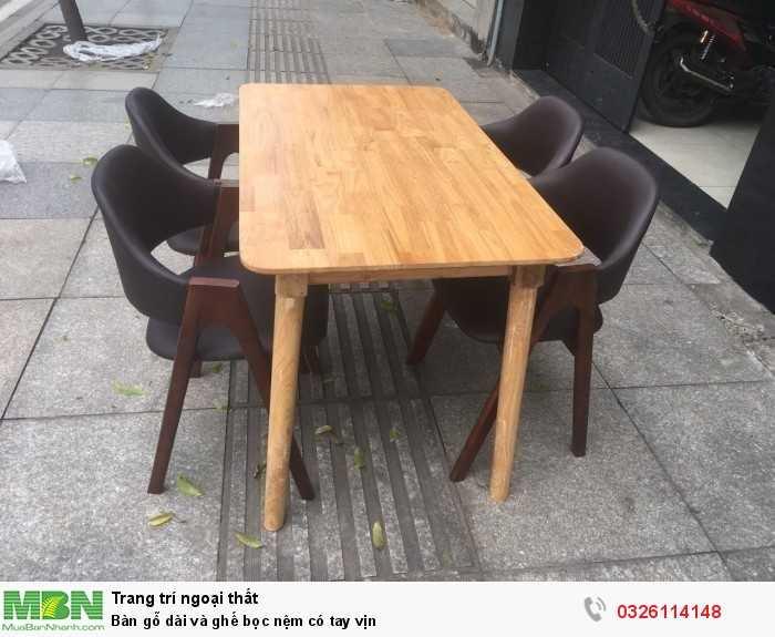 Bàn gỗ dài và ghế bọc nệm có tay vịn