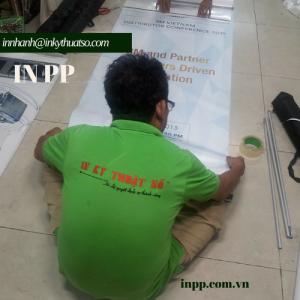 Nhân viên In Kỹ Thuật Số gắn poster vào banner cuốn cho khách hàng