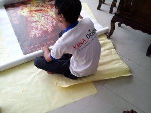 Nhân viên kiểm tra bề mặt tranh in và cuộn thành cuộn lớn, bọc cẩn thận trước khi giao hàng cho khách hàng | In tranh nghệ thuật, in tranh tôn giáo từ chất liệu silk tại In Kỹ Thuật Số