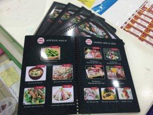In menu nhà hàng Love Sushi | Nền menu đen với hoa văn mây cuộn phong cách rất Nhật Bản cùng hình ảnh món ăn đặc trưng của đất nước Hoa Anh Đào là Maki Mono (Cơm cuộn kiểu Nhật), Age Mono (Đồ chiên kiểu Nhật) hoàn toàn nổi bật, tăng sự