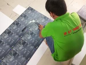 Thợ gia công in ấn thực hiện cắt thành phẩm menu PP cán format trước khi đóng thành cuốn