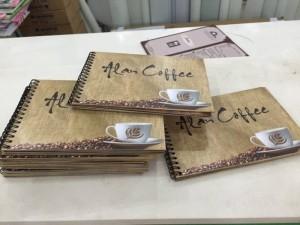 In menu quán cafe dạng cuốn cho Alan Coffe, họa tiết bao bố đựng cafe, hạt cafe đen rang xay nguyên chất được giữ nguyên cho cuốn menu thêm thu hút và đậm chất