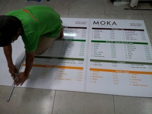 In menu áp tường cho quán cafe tại TPHCM - Nhân viên gia công cắt thành phẩm menu được in xong
