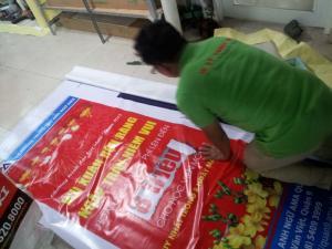 Nhân viên In Kỹ Thuật Số đang tiến hành gia công poster xuân Hiflex treo giá standee cho khách hàng