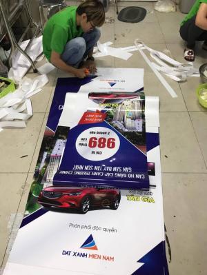 Gia công lắp 2 đầu poster vào banner cuốn - thực hiện bởi nhân viên gia công In Kỹ Thuật Số