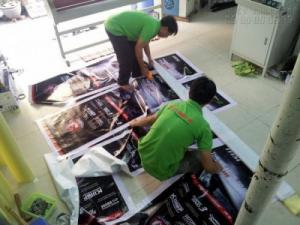 Nhân viên gia công In Kỹ Thuật Số thực hiện cắt thành phẩm, cuốn biên trước khi giao hàng đến khách đặt in