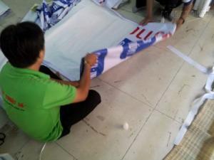 Nhân viên gia công In Kỹ Thuật Số thực hiện cuốn biên tấm banner in thành phẩm từ bạt hiflex