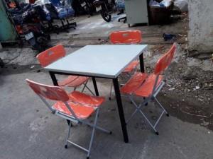 Bộ bàn gỗ màu trắng và ghế xếp màu đỏ