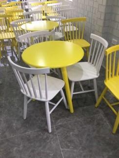 Bàn gỗ mặt tròn màu vàng chanh với ghế gỗ trắng