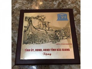 Kỷ vật do Chủ tịch tỉnh Bắc Giang tặng bằng đồng và gỗ tự nhiên, 1 mặt là hình ảnh Chùa Vĩnh Nghiêm