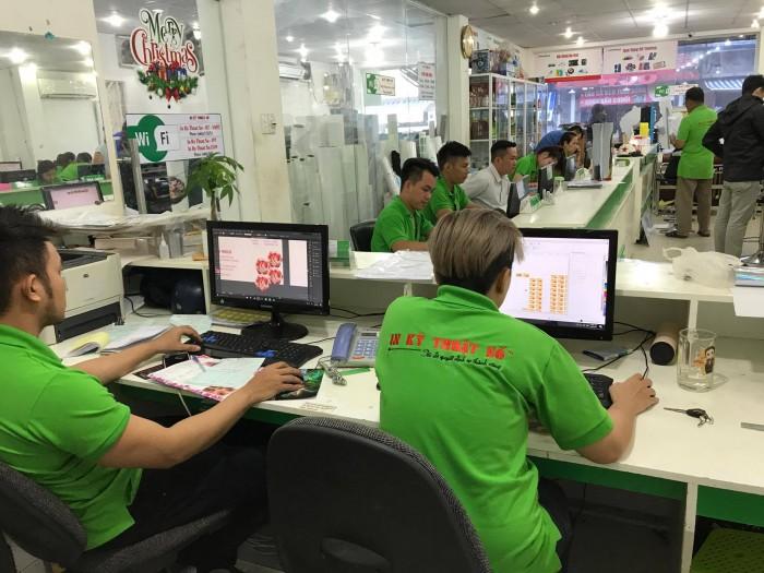 Nhân viên công ty in ấn hỗ trợ khách hàng kiểm tra hoặc thiết kế mới file in