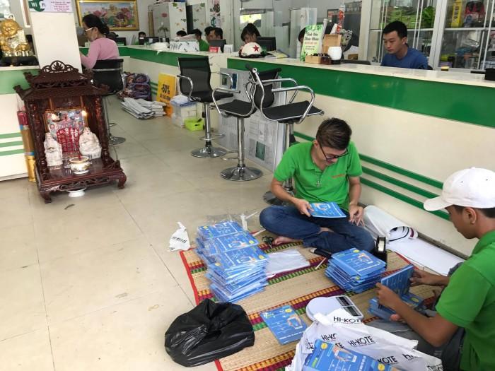 Nhân viên gia công hàng in hỗ trợ bao bọc ni lông cho brochure cho đơn hàng sự kiện