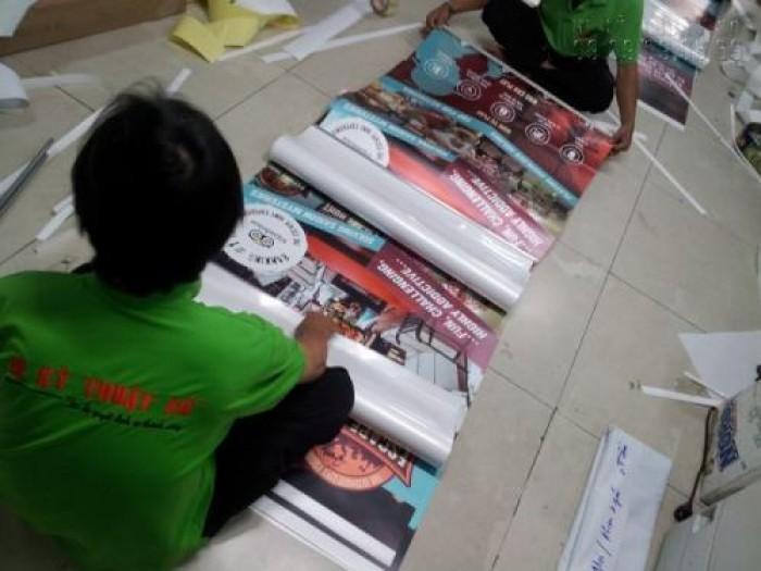 Nhân viên gia công lắp poster vào banner cuốn sẵn cho khách hàng