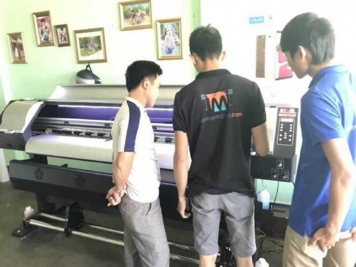 Nhân viên công ty phân phối máy in hướng dẫn khách hàng sử dụng máy in decal